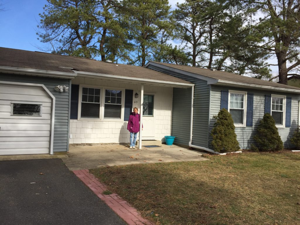 Me standing in front of my new home in Whiting NJ. It is one story, slate blue and white, with an attached garage.